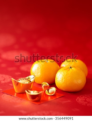 Chinese New Year - Mandarin orange, gold sycee (Foreign text means wealth) and red packet - stock photo
