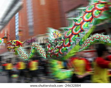 Chinese New Year Parade with Motion Blur as the Dragon speeds and twirls through City Streets to bring in year of the Ox - stock photo