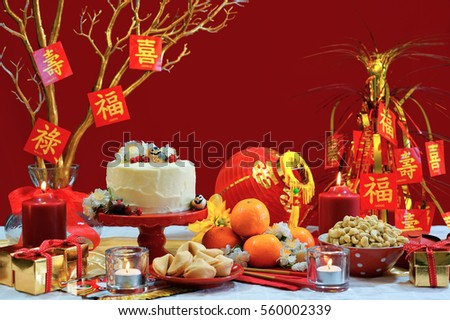 Chinese New Year party table in red and gold theme with food and traditional decorations.