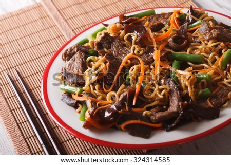 Chinese noodles with beef, muer and vegetables close-up on a plate. horizontal