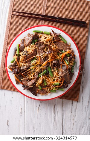 Chinese noodles with beef, muer and vegetables close-up on a plate. vertical top view