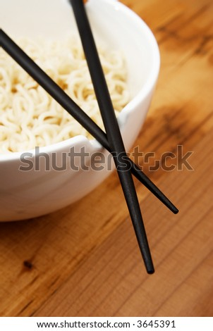 Chinese noodles with chop sticks in a bowl on wooden counter - stock photo