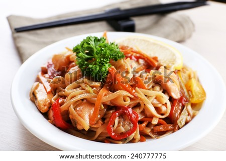 Chinese noodles with vegetables and seafood on plate on bamboo mat background - stock photo