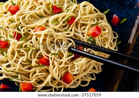 Chinese noodles with vegetables served on a blue dish - stock photo