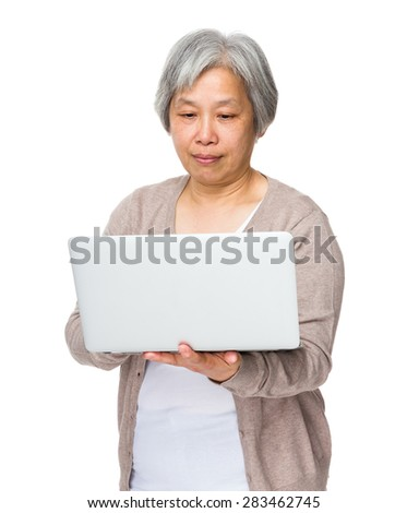 Chinese old woman use of notebook computer - stock photo