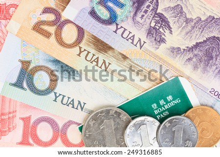 Chinese or Yuan banknotes money and coins from China's currency with boarding pass visa for travel concept, close up view as background - stock photo