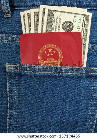Chinese passport and dollar bills in the back jeans pocket - stock photo