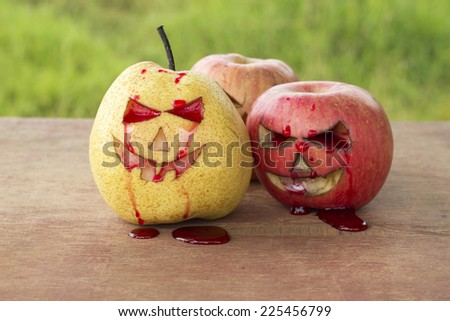 Chinese pear and apple for halloween on wood background - stock photo
