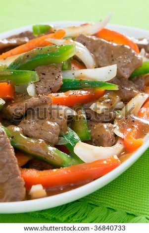Chinese pepper steak - slices of tender beef stir-fried with red and green bell peppers and onions. - stock photo
