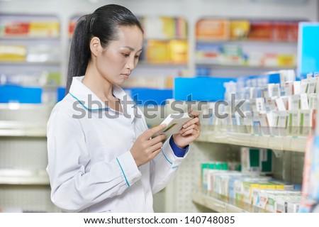 chinese pharmacist chemist woman choosing tablets in china pharmacy drugstore - stock photo