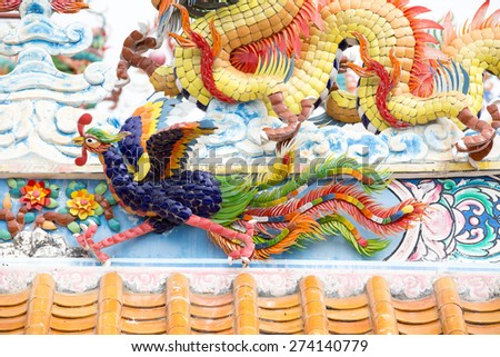Chinese Phoenix statue above the entrance to a Chinese temple. - stock photo
