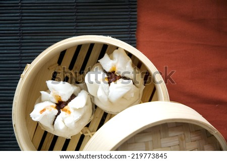 chinese pork bun in bamboo tray put on black and red background - stock photo