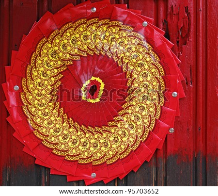 Chinese red packet known as ang pow arranged in a circular fan during Chinese New Year as a feng hui charm for prosperity on a red timber wall. - stock photo