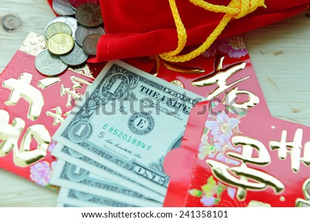Chinese Red Packet with US Dollar Notes , receiving lucky money packet. Chinese New Year tradition. - stock photo