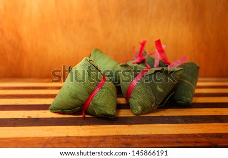 Chinese Rice Dumplings on chopping board with wooden background - stock photo