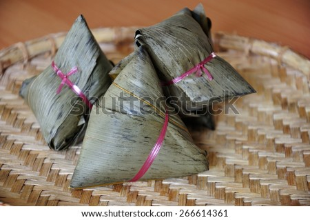 Chinese rice dumplings or zongzi a traditional Chinese food, made of glutinous rice stuffed with different fillings and wrapped in bamboo, reed or large flat leaves. Its served during festival. - stock photo