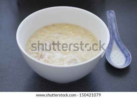 Chinese rice porridge with chicken pieces in a white bowl with a spoon - stock photo