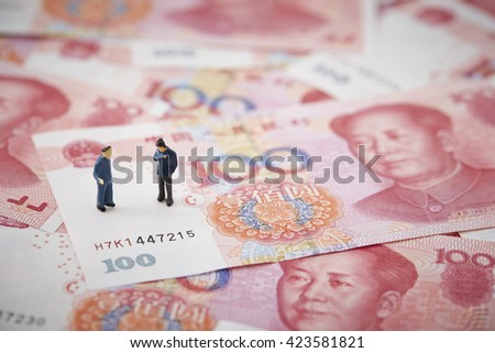 Chinese RMB bills and miniature men - stock photo