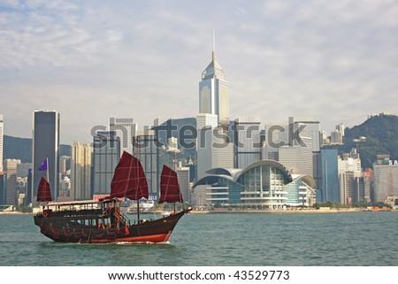 Chinese sailing ship and Hong Kong Convention and Exhibition Centre in Hong Kong Victoria Harbor  - stock photo