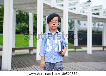 Chinese school boy holding a study book - stock photo