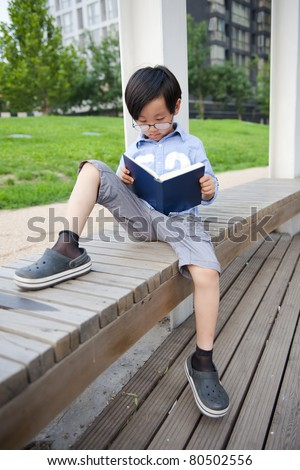 Chinese school boy reading a book - stock photo