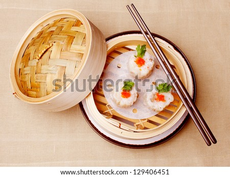 Chinese seafood dumplings garnished with red caviar and fresh parsley - stock photo