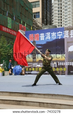 Chinese soldier waving a red flag - stock photo