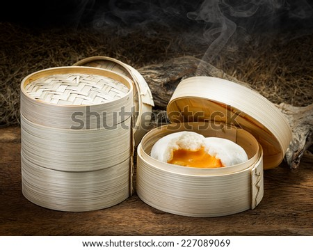 Chinese steamed bun and sweet creamy stuff in bamboo ware - stock photo