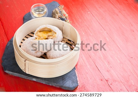 Chinese steamed bun and sweet creamy stuff set with  a cup of hot tea  on black stone and red background
