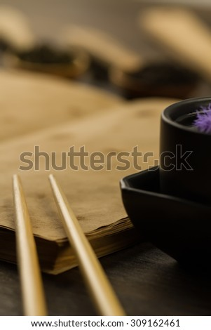 Chinese sticks on old blank open book on wooden background. Menu, recipe, mock up - stock photo