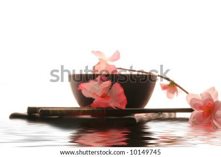 Chinese sticks, red plate and red cup in water - stock photo