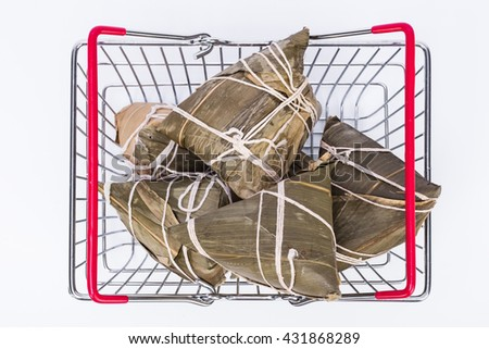 Chinese sticky rice dumplings (Zongzi) made of sticky rice, reed/bamboo leaf in a wire shopping basket, ussually taken during Traditional Food festival to celebrate Dragon Boat Festival. - stock photo