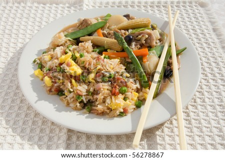 chinese stir-fry and ham fried rice dish with chopsticks - stock photo