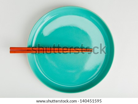 chinese style chopsticks put on green dish top view close up - stock photo