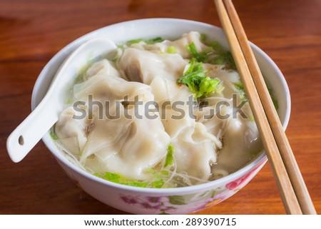Chinese tasty wonton and noodle soup on white background. - stock photo
