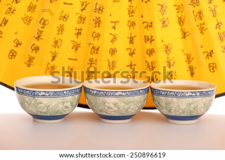 Chinese tea ceremony. Closeup image of traditional porcelain cups with tea with Chinese hand fan on the background - stock photo