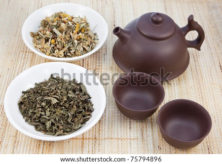 Chinese tea set with herbal teas on natural matting. - stock photo