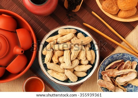 Chinese tea with peanuts on the wood table - stock photo