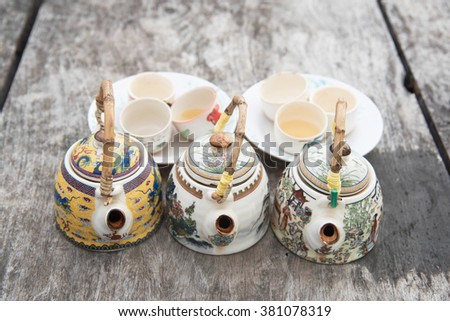 Chinese teapot and cups on wood table - stock photo