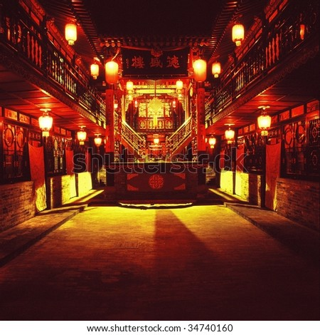 Chinese traditional courtyard in the ancient city of Pingyao, shanxi province, red lantern is main element, a stage in the middle is necessary for people to entertain - stock photo