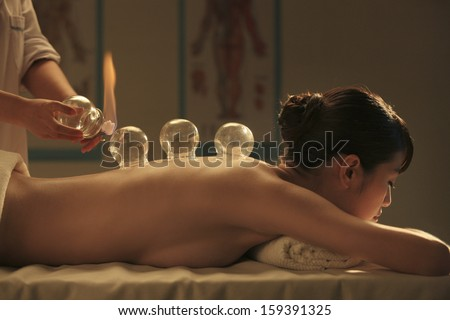 Chinese traditional herbalist doctor taking patient's pulse - stock photo