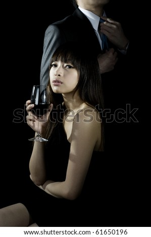 Chinese woman drinking wine with man in background - stock photo