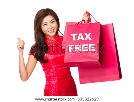 Chinese woman hold with shopping bag and thumb up for showing tax free - stock photo