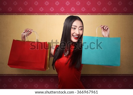 Chinese woman in cheongsam dress holding shopping bag. Chinese new year sale concept - stock photo