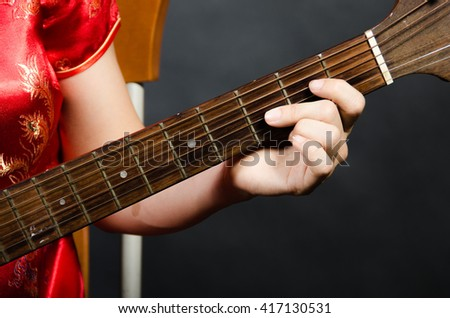 Chinese woman in nation red dress with guitar