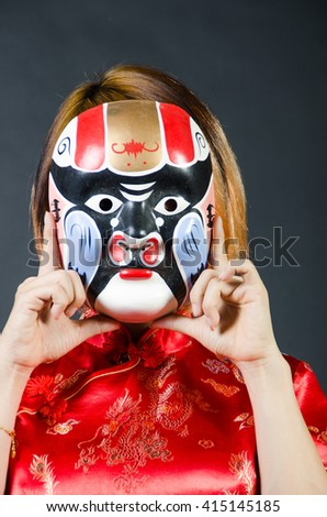 chinese woman in red National dress with monkey mask