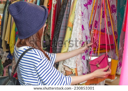 Chinese woman looking through handbags on racks at a street market in Taipei