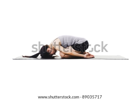Chinese woman on a yoga mat doing the childs pose. - stock photo