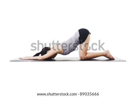 Chinese woman on a yoga mat doing the extended puppy pose. - stock photo
