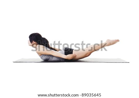 Chinese woman on a yoga mat doing the locust pose. - stock photo